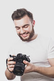 Young bearded photographer taking pictures with digital camera. Stock Photo