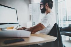 Young bearded professional architect wearing eye glasses working at modern loft studio-office with desktop computer Royalty Free Stock Photo