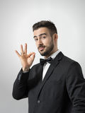 Young bearded restaurant waiter showing delicious hand gesture looking at camera. Stock Photo
