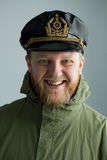 Young bearded sailor. Cap and green jacket Royalty Free Stock Images