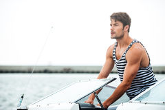 Young bearded sailor man driving his motor boat Stock Photos