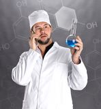 Young bearded scientist in white uniform gown coat and hat. With blue liquid in a flask posing in studio over chemical formula Stock Images
