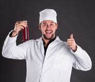 Young bearded scientist in white uniform gown coat and hat with. Red liquid in a flask posing in studio Royalty Free Stock Photo