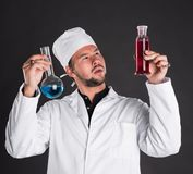 Young bearded scientist in white uniform gown coat and hat with. Liquid in a flasks posing in studio Royalty Free Stock Photos