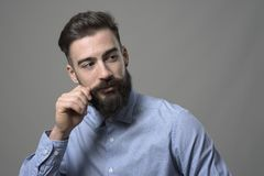 Young bearded smart casual hipster twirling mustache and looking back over the shoulder at copyspace. Against gray background royalty free stock photos