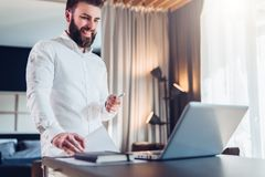 Young bearded smiling businessman in white shirt is standing near desk in front of laptop, holding in his hand documents. Pen, looking at computer screen Stock Image
