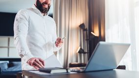 Young bearded smiling businessman in white shirt is standing near desk in front of laptop, holding in his hand documents. Pen, looking at computer screen Royalty Free Stock Images