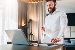 Young bearded smiling businessman in white shirt is standing near desk in front of laptop, holding in his hand documents. Pen, looking at computer screen Stock Photos
