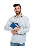 Young bearded smiling man with books in hands on white Royalty Free Stock Images