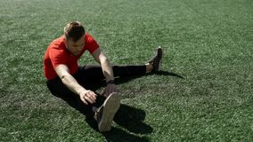 Young man does stretching on stadium lawn stock video
