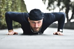 Healthy lifestyle concept. Muscular athlete exercising push up outside in city park. royalty free stock photography