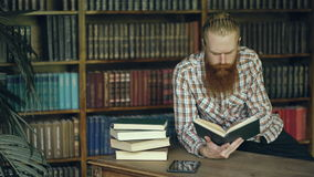 Young bearded student in library reading a book and prepare for exams. Young bearded man in library reading a book and prepare for exams stock video footage