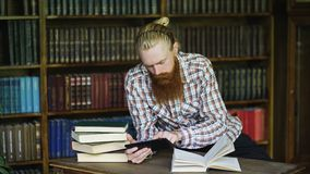 Young bearded student in library reading a book and using tablet computer to prepare for exams. Young bearded student in library reading a book and using tablet Royalty Free Stock Photo