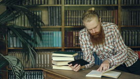 Young bearded student in library reading a book and using tablet computer to prepare for exams stock footage