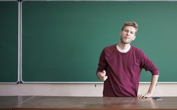 Young bearded student sits on teacher table desk in front of blackboard with copy space. Young bearded student sits on the teacher table desk in front of Stock Photos