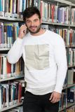Student Talking on the Phone in Library. Young Bearded Student Talking Phone While Preparing for Exams in Univercity Library Stock Image