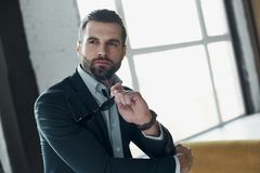 Young stylish businessman leader indoors at office holding sungl. Young bearded stylish businessman leader indoors at office sitting looking aside holding stock image