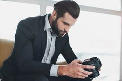Young stylish businessman leader indoors at office looking at pictures on camera. Young bearded stylish businessman leader indoors at office sitting on sofa Royalty Free Stock Photography