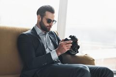 Young stylish businessman leader indoors at office wearing sunglasses checking photos on camera. Young bearded stylish businessman leader indoors at office Royalty Free Stock Images