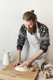 Young bearded stylish man in the kitchen with apron making dough for pasta with white flour and eggs Stock Photography