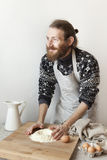 young bearded stylish man in the kitchen with apron making dough for pasta with white flour and eggs Stock Photos