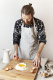 young bearded stylish man in the kitchen with apron making dough for pasta with white flour and eggs Royalty Free Stock Photo