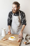 Young bearded stylish man in the kitchen with apron making dough for pasta with white flour and eggs Royalty Free Stock Image