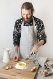 Young bearded stylish man in the kitchen with apron making dough for pasta with white flour and eggs Stock Images