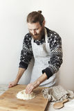 Young bearded stylish man in the kitchen with apron making dough with white flour Stock Photography