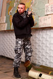 Terrorist with a gun in the stroma of a dilapidated shelter Stock Photo