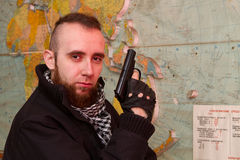 Young bearded terrorist. With a gun in the stroma of a dilapidated shelter, the basement of the old building Stock Photo