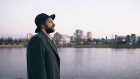 Young bearded tourist man in hat and coat watching cityscape and daydreaming while standing on riverside stock photography