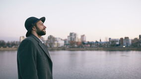 Young bearded tourist man in hat and coat watching cityscape and daydreaming while standing on riverside