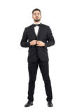 Young bearded wealthy man buttoning tuxedo with bow tie. Royalty Free Stock Image