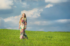 Young beatiful girl in green field Royalty Free Stock Image