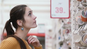 Young beatifull woman standing in front of cups in the supermarket shop and try to choose something. 4K stock footage