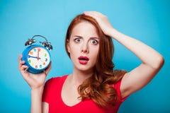 Young beautfiul redhead girl with alarm clock stock images