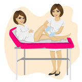 Young beautician waxing young woman legs lying on spa bed Stock Photos