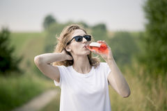 Young beautifil woman drinking red softdrink. Stock Image