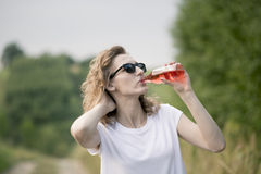 Young beautifil woman drinking red softdrink. Royalty Free Stock Photos