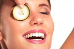 Young beautiflul smiling girl applying a cucumber beauty treatme Stock Photos