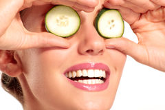 Young beautiflul smiling girl applying a cucumber beauty treatme Stock Image