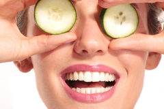 Young beautiflul smiling girl applying a cucumber beauty treatme Royalty Free Stock Photography