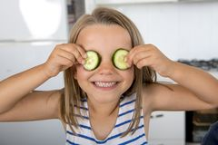 Young beautiful and adorable girl 6 or 7 years old having fun at home kitchen putting cucumber slices on her eyes smiling happy. In children lifestyle concept Stock Photography
