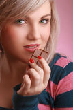 Young beautiful adult with chocolate. Beautiful young woman bites a chocolate and looking at camera Royalty Free Stock Images