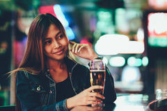 Young beautiful adult girl in a club drinking beer alone Royalty Free Stock Image