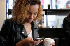 A young beautiful African-American woman in a leather jacket with a white paper glass in one hand looks into the phone. Close-up p royalty free stock photo