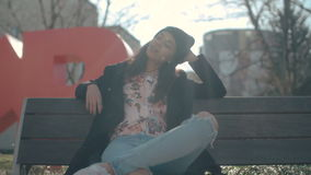 Young beautiful african american woman sitting on a bench. Stylish woman relaxing in a city during sunny day stock video