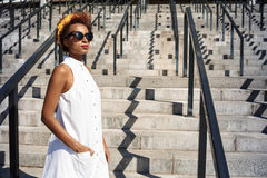 Young beautiful african girl going up stairs walking down city. Stock Photos