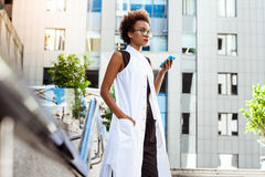 Young beautiful african girl holding phone walking down city. Young beautiful african girl in glasses holding phone walking down city. Fashion street style Stock Image